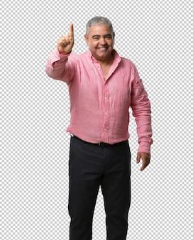 Homem de meia idade mostrando o número um, símbolo de contagem, matemática, confiante e alegre