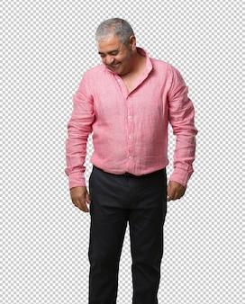 Homem de meia idade rindo e se divertindo, sendo relaxado e alegre, sente-se confiante e bem sucedido
