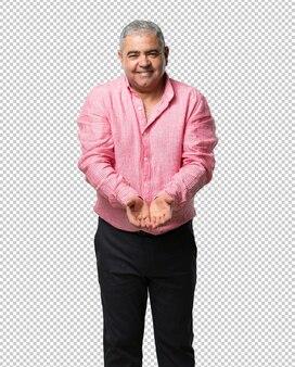 Homem de meia idade segurando algo com as mãos, mostrando um produto, sorridente e alegre, oferecendo um objeto imaginário
