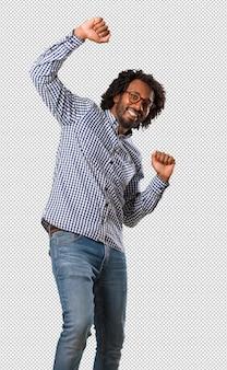 Homem de negócios americano africano bonito ouvir música, dançar e se divertir, movendo-se