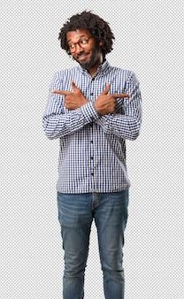 Homem de negócios americano africano confuso e duvidoso homem bonito, decidir entre dois optio