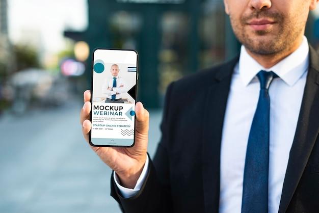 Homem de negócios ao ar livre segurando uma maquete de telefone