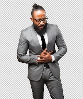 Homem de negócios preto que sofre de dor de estômago