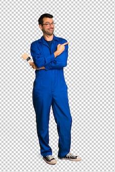 Homem de pintor apontando para o lado para apresentar um produto