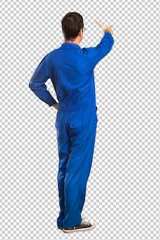 Homem de pintor apontando para trás com o dedo indicador