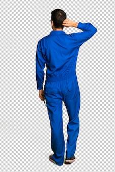 Homem de pintor na posição traseira, olhando para trás enquanto coçando a cabeça