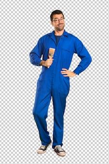Homem de pintor posando com os braços no quadril e sorrindo