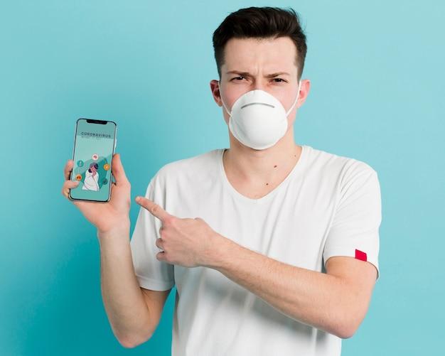 Homem de prevenção de coronavírus, apontando para o seu telefone móvel