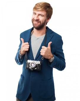 Homem de sorriso com uma câmera velha