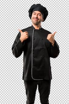 Homem do cozinheiro chefe no uniforme preto dando os polegares acima do gesto com ambas as mãos e sorriso.