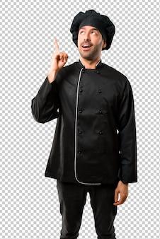 Homem do cozinheiro chefe no uniforme preto que está e que pensa uma ideia que aponta o dedo acima