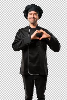 Homem do cozinheiro chefe no uniforme preto que faz o símbolo do coração pelas mãos. estar apaixonado