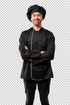 Homem do cozinheiro chefe no uniforme preto que mantém os braços cruzados na posição frontal. expressão confiante