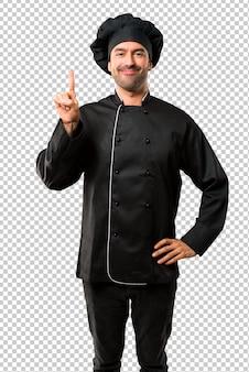 Homem do cozinheiro chefe no uniforme preto que mostra e que levanta um dedo no sinal do melhor
