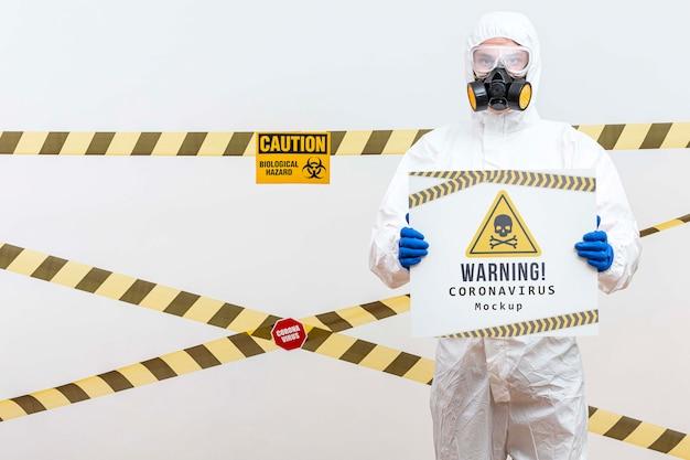 Homem em traje de proteção, segurando um modelo de aviso de coronavírus