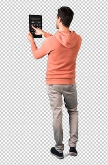 Homem em uma camisola cor-de-rosa que prende uma calculadora. máquina de contagem