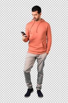 Homem em uma camisola rosa enviando uma mensagem ou e-mail com o celular