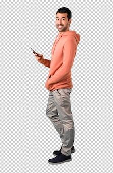 Homem em uma camisola rosa olhando para a câmera e sorrindo enquanto estiver usando o celular