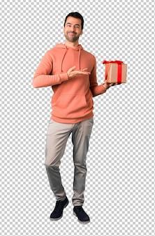 Homem em uma camisola rosa segurando caixas de presente nas mãos