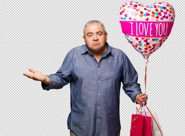 Homem envelhecido médio comemorando o dia dos namorados confuso e duvidoso