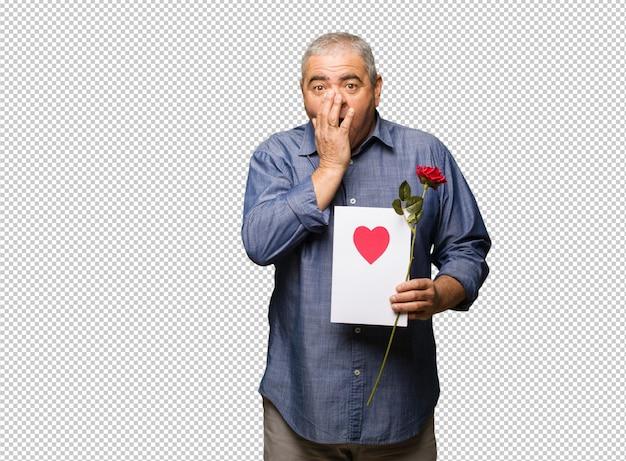 Homem envelhecido médio comemorando o dia dos namorados muito assustado e com medo escondido