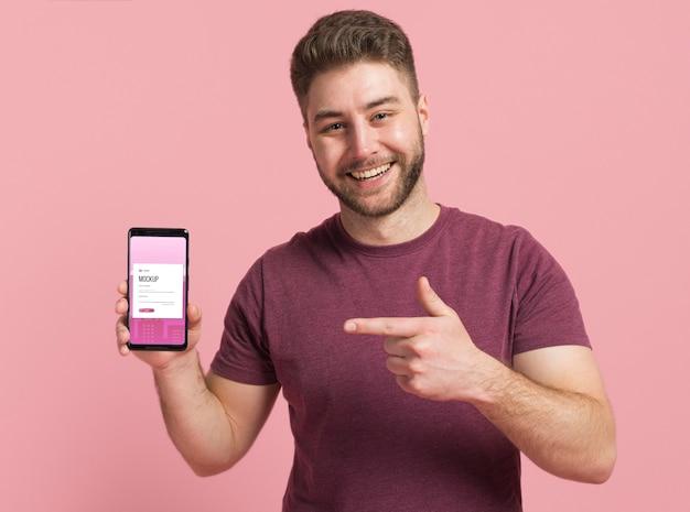Homem feliz mostrando maquete digital de smartphone