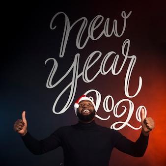Homem feliz, mostrando os polegares para cima e fundo do ano novo 2020