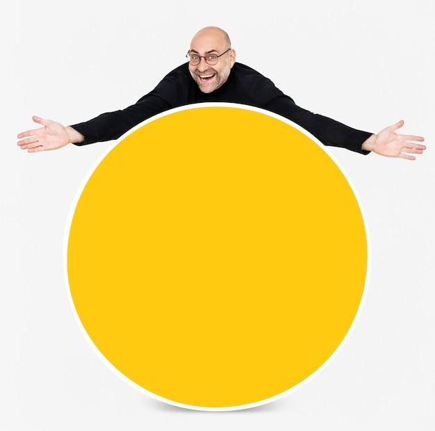 Homem feliz, mostrando uma placa amarela redonda