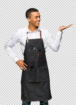 Homem jovem afro-americano barbeiro segurando copyspace imaginário na palma da mão para inserir um anúncio