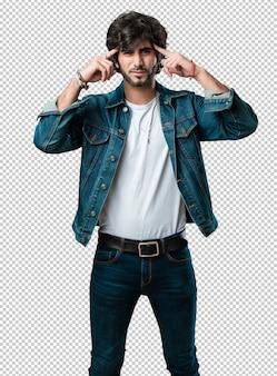 Homem jovem bonito, fazendo um gesto de concentração, olhando para a frente, focado em um objetivo