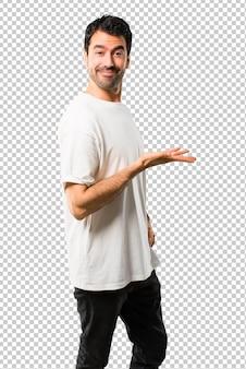 Homem jovem, com, camisa branca, apresentando, um, produto, ou, um, idéia, enquanto, olhar, sorrindo, direção