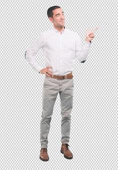 Homem jovem confiante apontando com a mão - foto de corpo inteiro