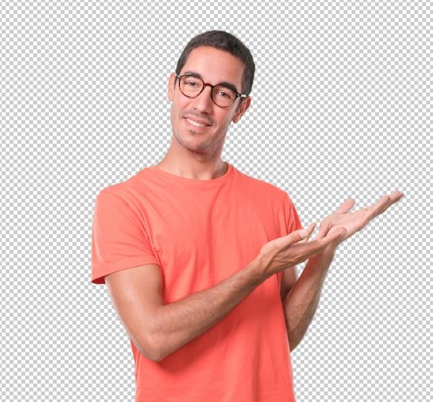 Homem jovem confiante mostrando algo com a mão
