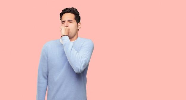 Homem jovem e bonito tosse, sofrendo uma doença de inverno, como um resfriado ou gripe