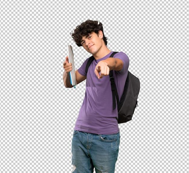 Homem jovem estudante aponta o dedo para você enquanto sorrindo