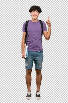 Homem jovem estudante apontando para cima e surpreso