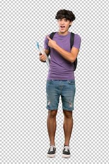 Homem jovem estudante surpreso e apontando o lado