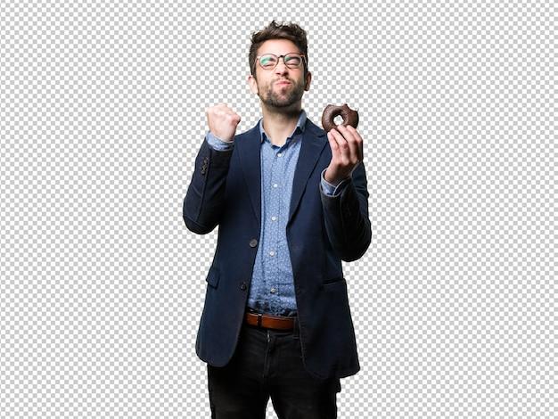 Homem jovem, fazendo, vencedor, gesto, e, segurando, um, donut