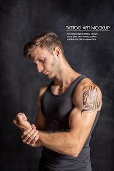 Homem jovem fitness mostrando tatuagem na parte superior do braço em um ginásio escuro