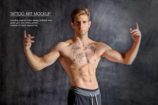 Homem jovem fitness mostrando tatuagem no peito em um ginásio escuro