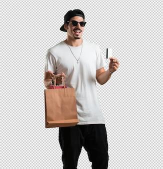 Homem jovem rapper alegre e sorridente, muito animado, segurando o novo cartão bancário e sacolas de compras, pronto para ir às compras