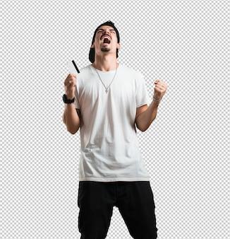 Homem jovem rapper alegre e sorridente, muito animado, segurando o novo cartão do banco, pronto para ir às compras