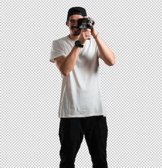Homem jovem rapper animado e entretido, olhando através de uma câmera de filme, procurando uma foto interessante, gravando um filme, produtor executivo