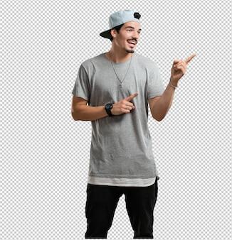 Homem jovem rapper apontando para o lado, sorrindo surpreso apresentando algo natural e casual