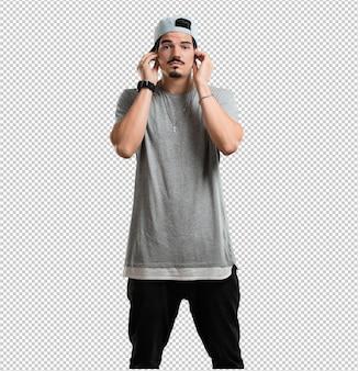 Homem jovem rapper cobrindo as orelhas com as mãos, irritado e cansado de ouvir algum som
