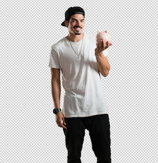 Homem jovem rapper confiante e alegre, segurando um banco leitão e ficar quieto porque o dinheiro é salvo.