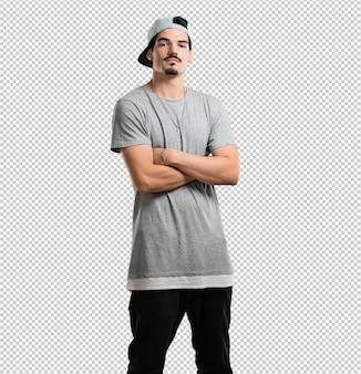 Homem jovem rapper cruzando os braços, sério e imponente, sentindo-se confiante e mostrando poder