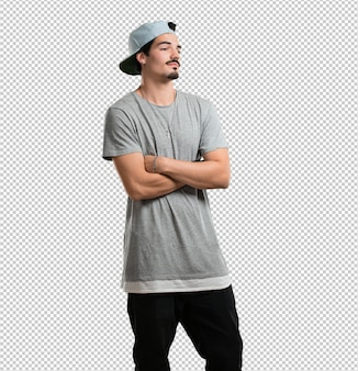 Homem jovem rapper cruzando os braços, sorridente e feliz, sendo confiante e amigável
