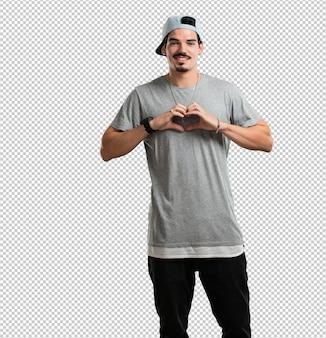 Homem jovem rapper fazendo um coração com as mãos, expressando o conceito de amor e amizade, feliz e sorridente