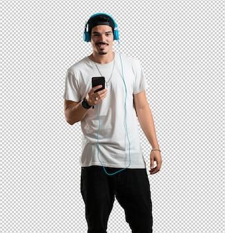 Homem jovem rapper feliz e divertido, ouvindo música, fones de ouvido modernos, feliz sentindo o som e o ritmo